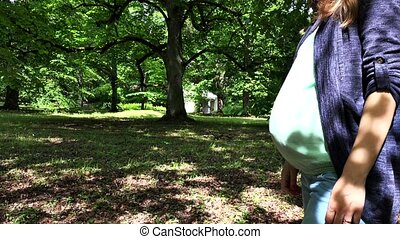 Pregnant girl caress her big belly tummy and walk in park....