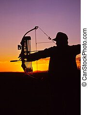 Bowhunter Shooting at Sunset - a bowhunter at full draw...