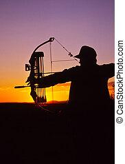 Bowhunter Shooting at Sunset