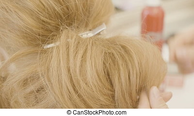 Hairdresser making a hairstyle in the salon on a blonde...