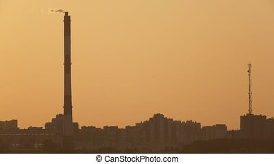 Big pipe on city skyline at sunset - industry view,...