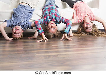 three childs laying upside down on a white sofa at home...