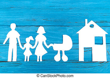 Paper silhouette of family with baby carriage, house on blue...