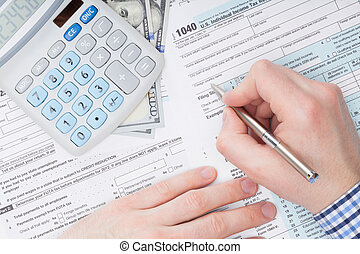 Close up shot of a male filling out US 1040 Tax Form next to...