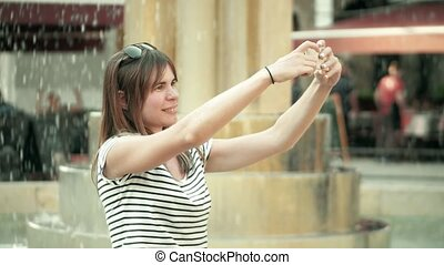 Smiling young woman making selfies with her smart phone near...