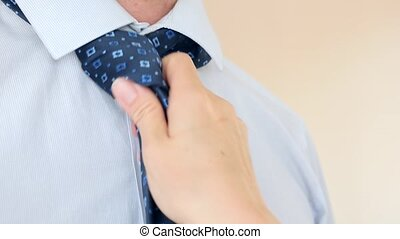 The female hand sexually corrects the blue tie around the...