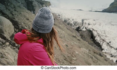 Young brunette woman standing on the mountain and looking on glaciers in Vatnajokull ice lagoon in Iceland.