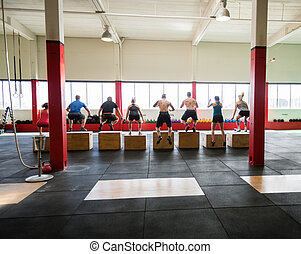 Clients Performing Box Jumps In Fitness Studio