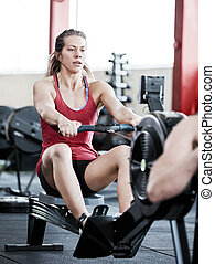Woman Using Rowing Machine In Gym - Young woman in...