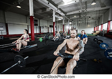 Muscular Man Working Out On Rowing Machine - Determined...