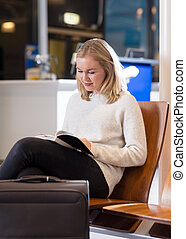 Woman Reading Book In Airport Waiting Area
