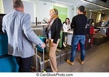 Airline Passengers Weighting Their Luggage At Airport