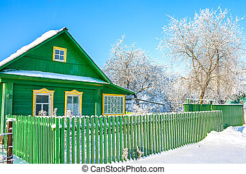 rural wooden house in winter covered with snow.