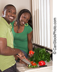 Young ethnic couple on kitchen slicing vegetables - Young...
