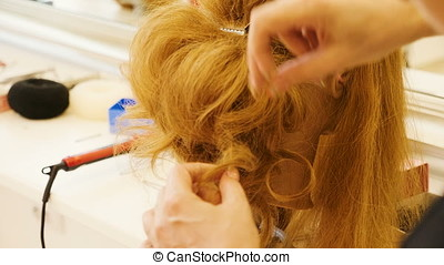 Hairdresser making a hairstyle in the salon on a redhair...