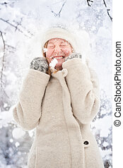 Winter portrait of a blond young woman in the snow - Snow...