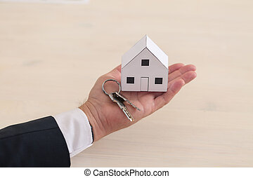 House and keys on hand - Close-up of paper house and keys on...
