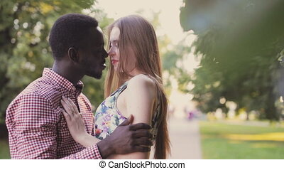 happy interracial couple in city park - cute interracial...