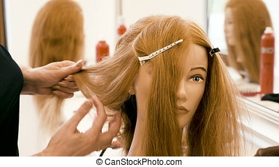Hairdresser making a hairstyle in the salon on a mannequin