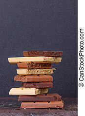 stack of different kind porous chocolate pieces on a dark...