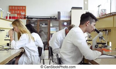 High school students with microscopes in laboratory. - Group...