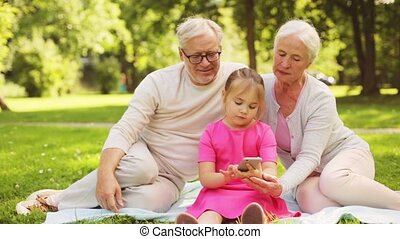 grandparents and granddaughter with smartphone - family,...