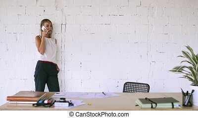 Businesswoman in her office with a smartphone. - Beautiful...