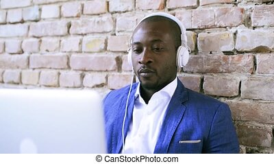 African businessman at the desk with headphones.