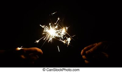 hands with burning sparklers in darkness - holidays,...