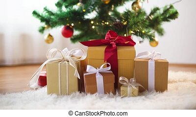 hands taking gift boxes from under christmas tree -...