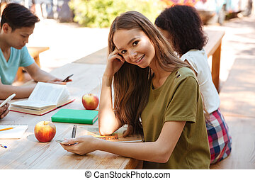 Side view of a pretty smiling woman sitting by table - Side...