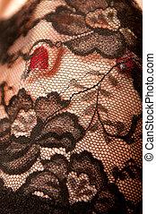 Red fingernail under black nylon stockings, narrow depth of...
