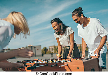 kicker - group of happy friends playing table football on...
