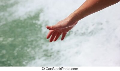 Hand glides over waves splashes water from speed boat....