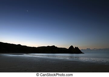 Three Cliffs Bay Gower - A waning crescent moon and a blue...