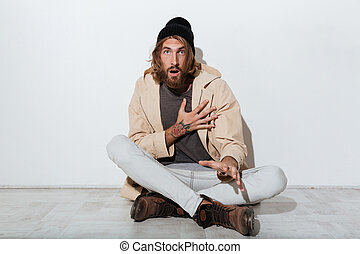 Shocked hipster man looking camera sitting isolated -...