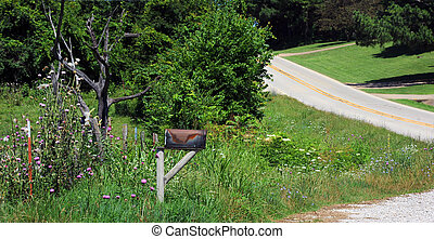 Backroad View in the Ozarks - Rusty metal mailbox sits on...