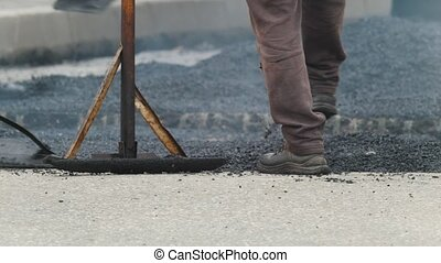 Workers are creating new asphalt - road construction in...