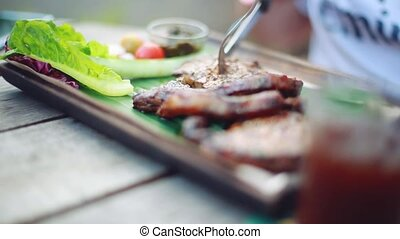 man cuts off a piece of steak and eats close up on blurred background outdoor cafe. 1920x1080