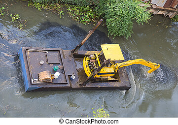 Small dredge doing maintenance on a canal - Small dredge, an...