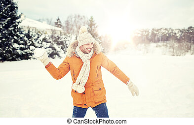 happy young man playing snowballs in winter - people, season...