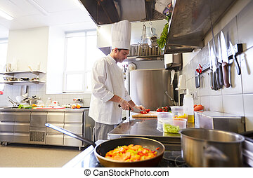 male chef cooking food at restaurant kitchen - cooking food,...