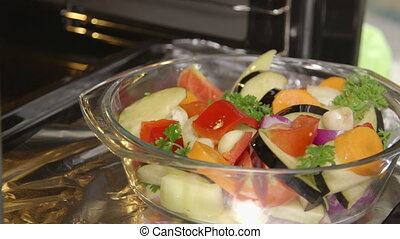 Cooking roasted vegetables in the oven closeup. Chef puts...