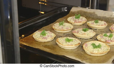 Cooking baked mini pizza with mozzarella cheese and ham in...