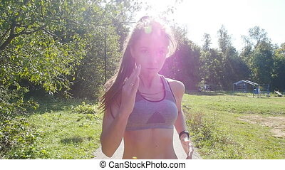 Pretty young sporty woman jogging at park