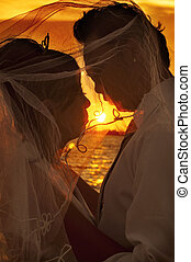 Wedding day - Couple kissing on beach during sunset