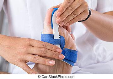 Orthopedist Fixing Plaster On Injured Man's Foot - Close-up...