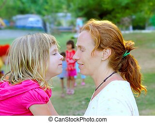 Mother and daughter profile playing in park