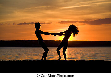 Excitement - Silhouettes of happy couple holding each other...