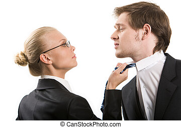 Conflict - Image of business woman holding by man?s tie and...
